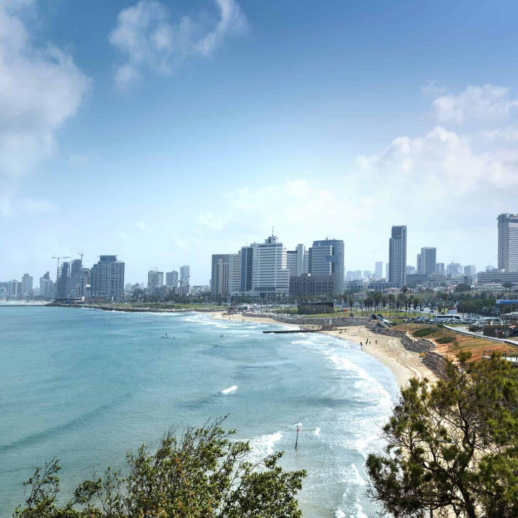 Tel Aviv skyline by day with beach, sea and waves